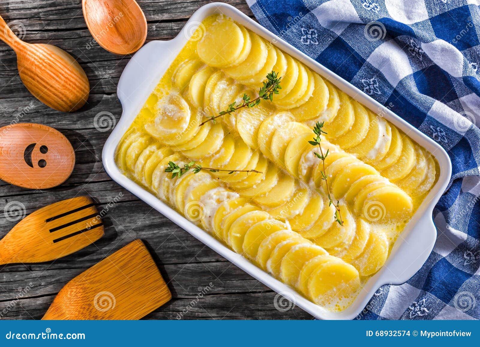 Gratinerade Dauphinois, potatisar som är förberedda för att grilla i en panna