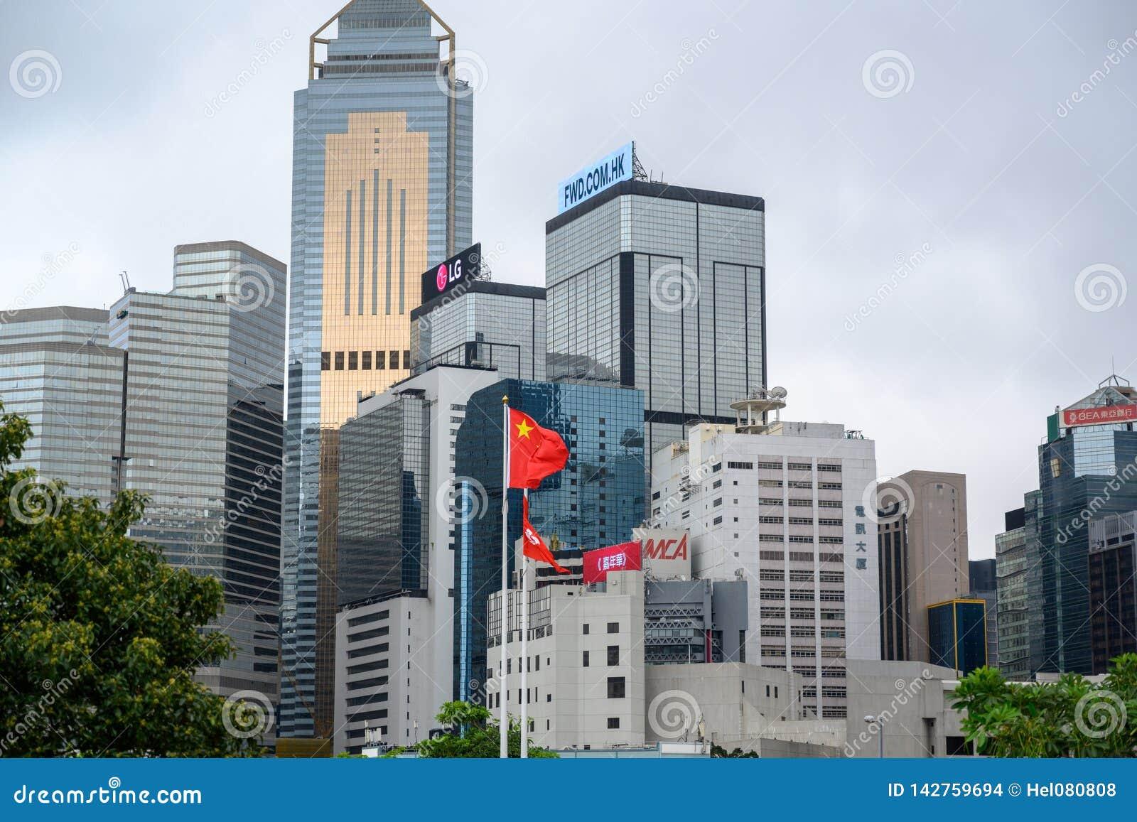 Gratte-ciel bâtiments ayant beaucoup d étages des sociétés de nternational avec le drapeau chinois dans l avant en Hong Kong Isla