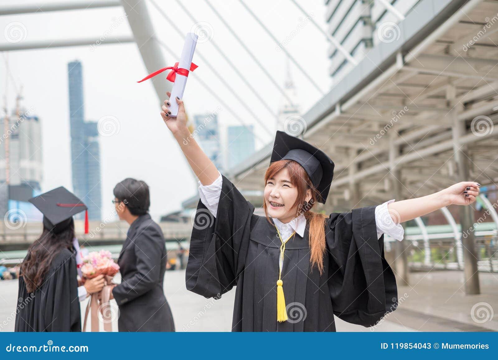 Grau graduado do ` s do licenciado da mulher que guarda o diploma com engodo dos pares