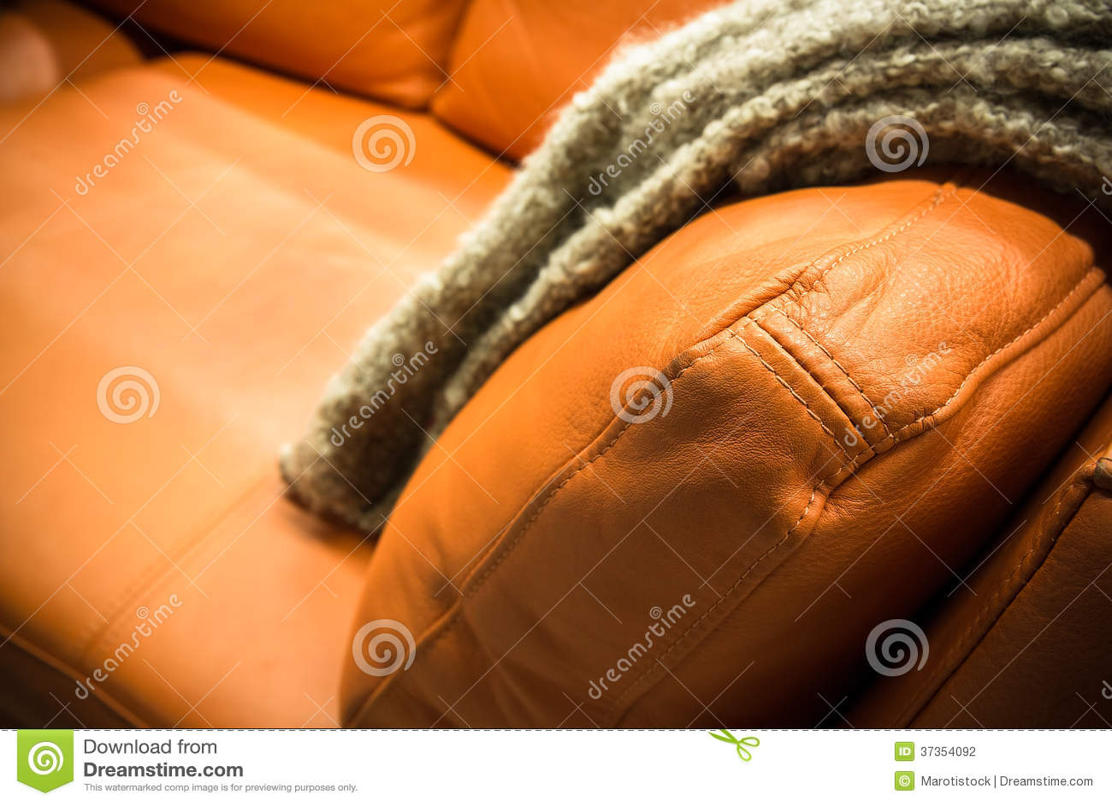 graue decke drapiert ber einer ledercouch. Black Bedroom Furniture Sets. Home Design Ideas