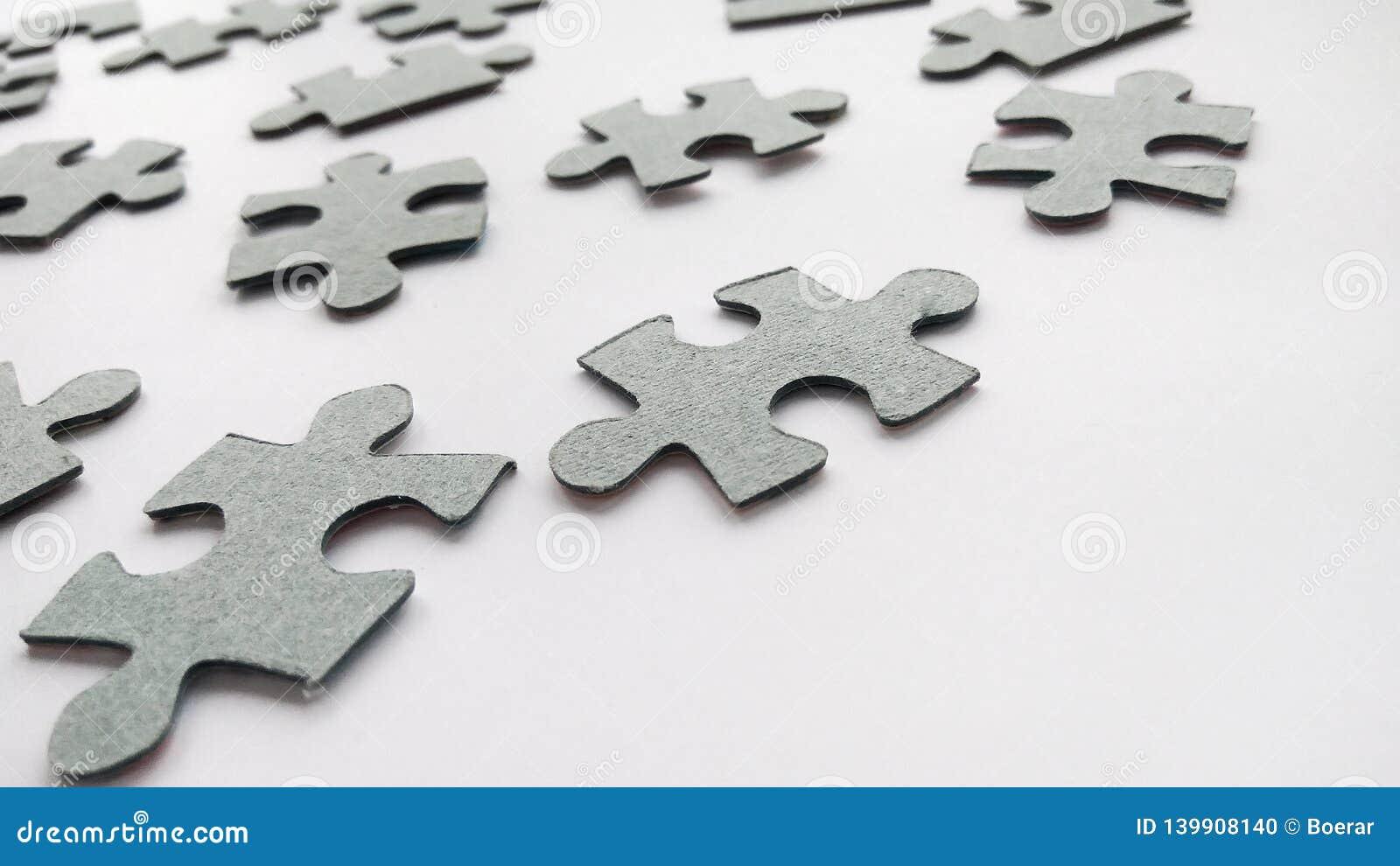 Graue Puzzlestücke der Zusammenfassung auf weißem Hintergrund