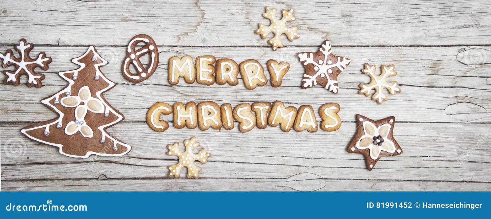 Grauer hölzerner Hintergrund Christmassy mit Lebkuchen und fröhlichem Christma-` s Buchstaben
