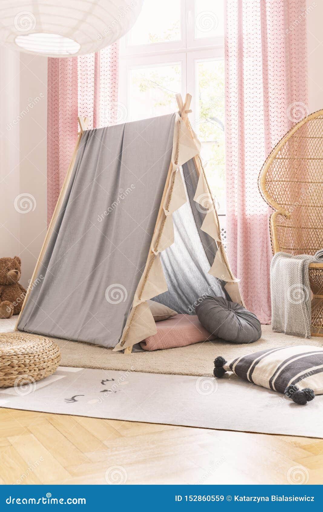Graues scandi Zelt im netten Spielzimmer des kleinen Mädchens mit Weidenpfaustuhl, Kissen und Teppichen, wirkliches Foto