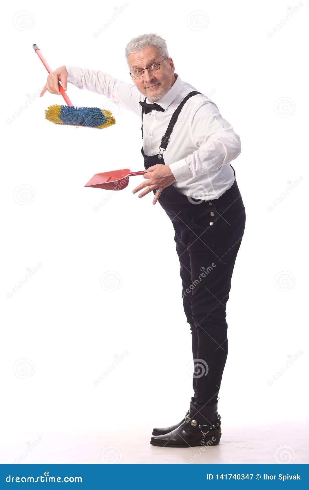 Grauhaariger Reiniger, Hausmeister in einem schwarzen Overall mit einem Mopp und Müllschippe erbringt Reinigungsdienstleistung, a