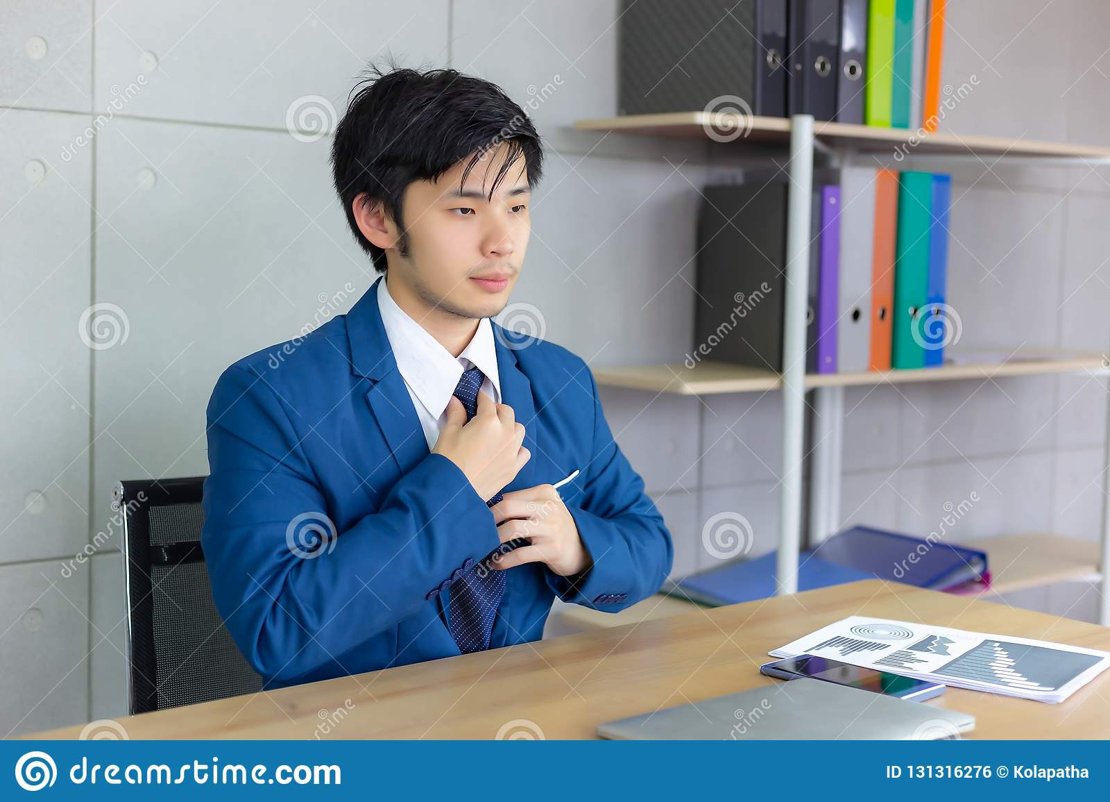 Gravata nova considerável dos laços do homem de negócios no escritório It's o fi