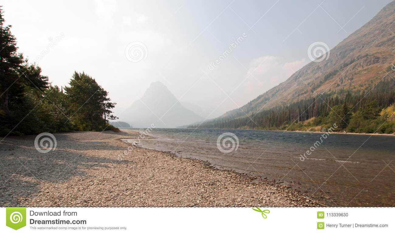 Gravelly shoreline of Upper Two Medicines Lake in Glacier National Park during the 2017 fall forest fires in Montana USA