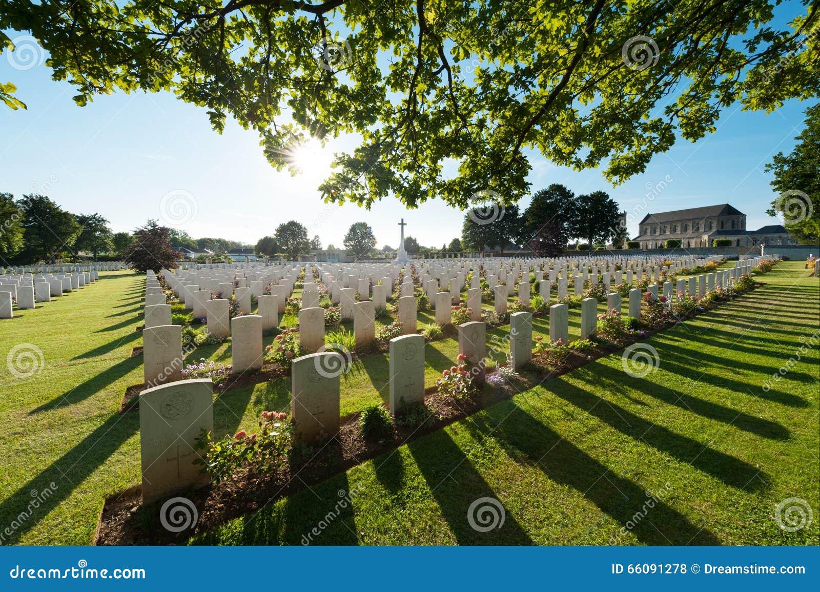 Graven en boom in achter-licht, in een Engelse militaire begraafplaats in Normandië, in Ranville