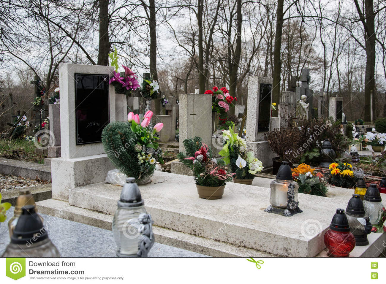 Graves, tombstones and crucifixes on traditional cemetery. Votive candles lantern and flowers on tomb stones in graveyard