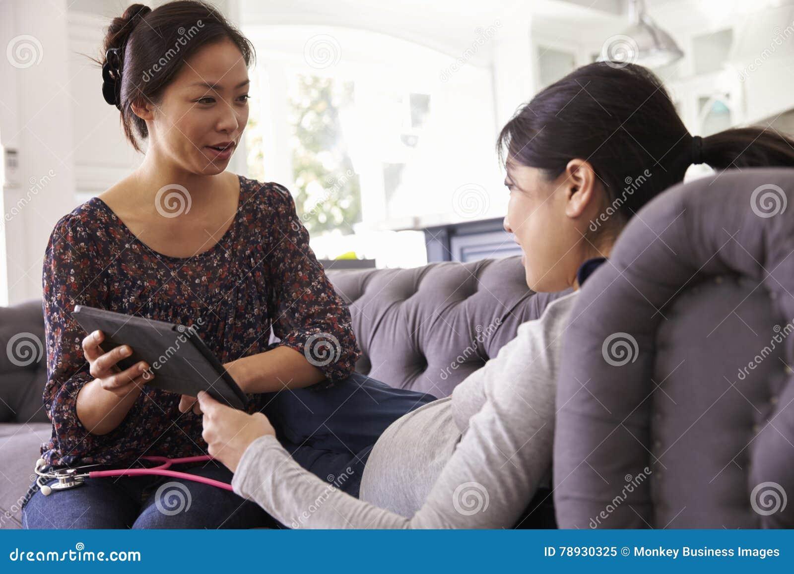 Gravid kvinna som hemma undersöks av barnmorskan