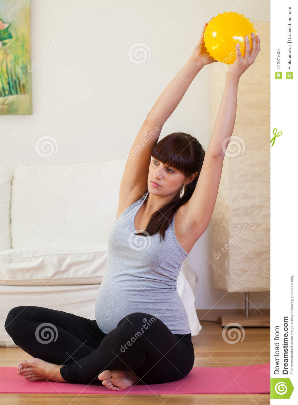 Gravid woman doing exercises at home