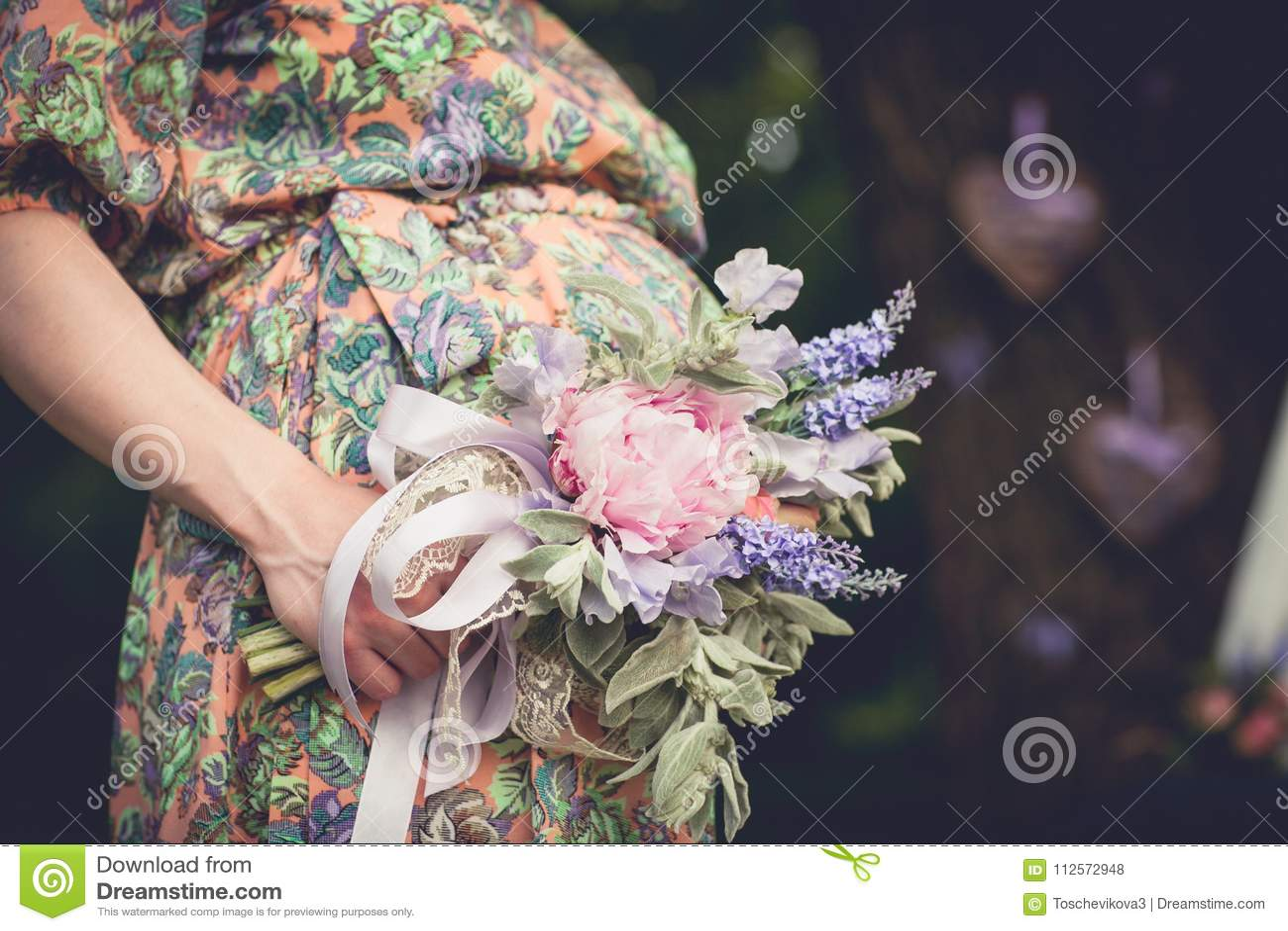 Gravida kvinnan med den ljusa sommarbuketten av blommor rymmer händer på buken på en solig dag utomhus Havandeskap föräldraskap,