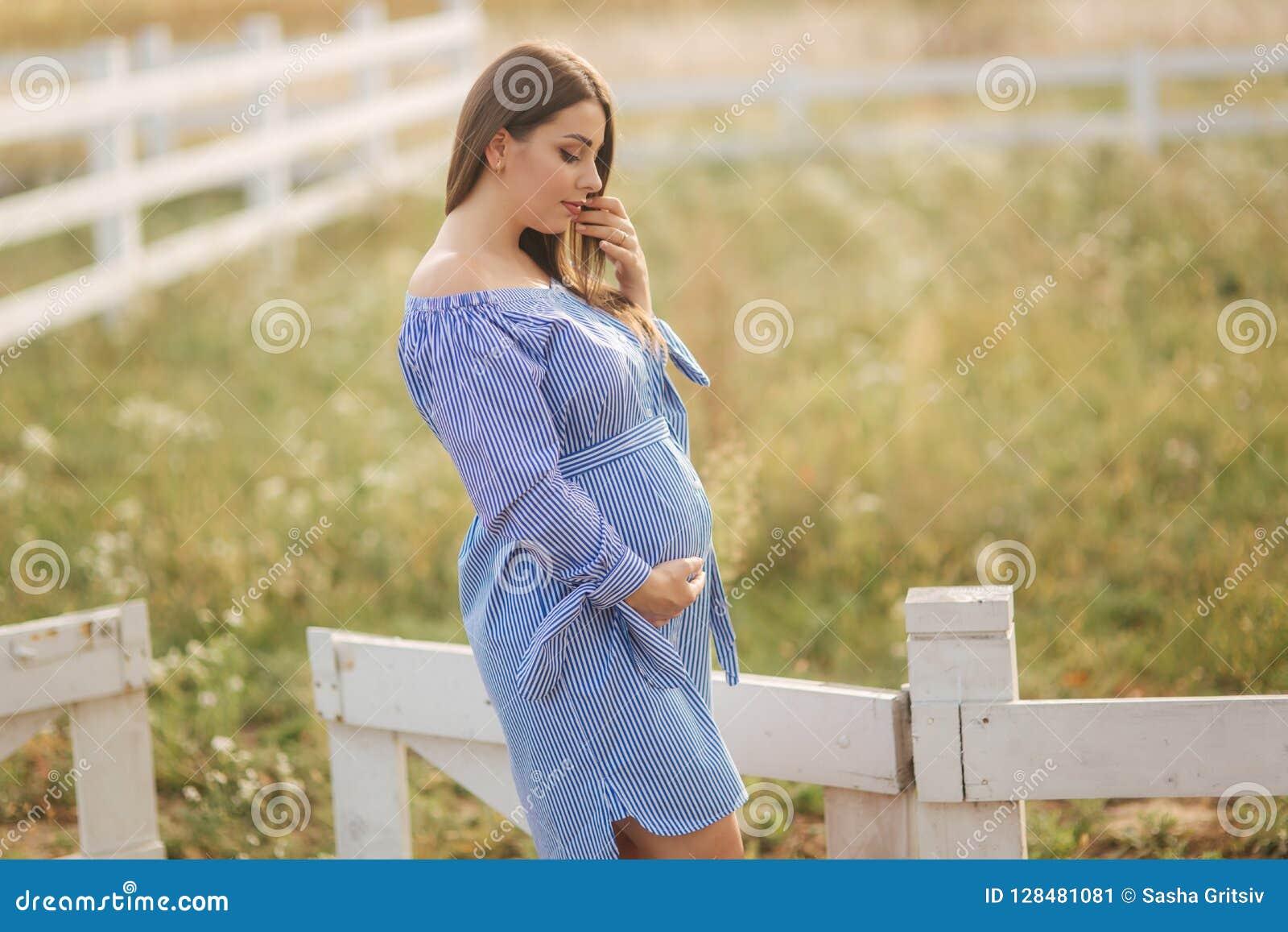 Gravida kvinnan satte handen på hennes buk och smekning Härlig framtida moder