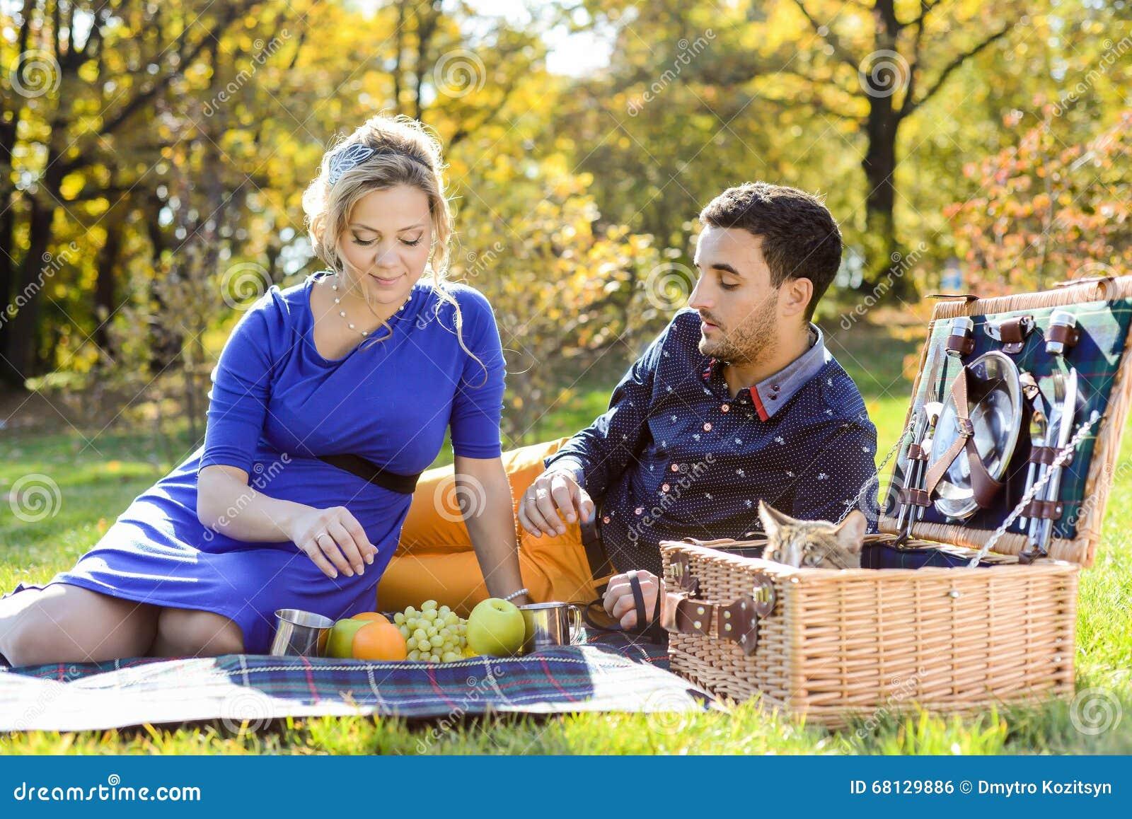 Gravida lyckliga och le par på picknick med katten