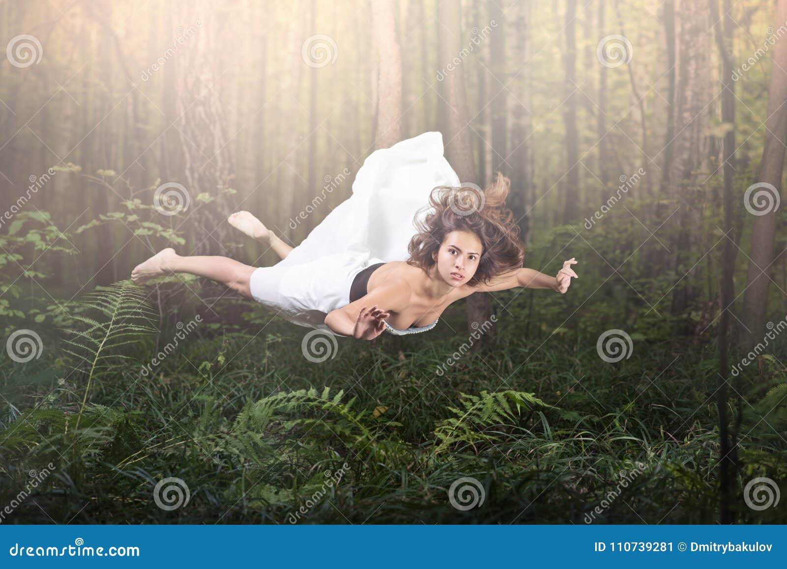 Gravidade zero Voo bonito novo da mulher em um sonho Verde floresta e fulgor