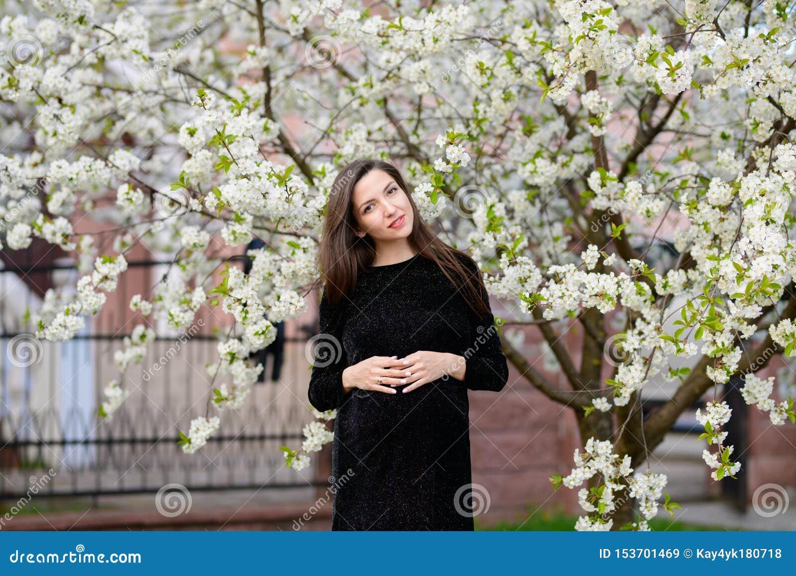 Gravidanza di estate Bella donna incinta Giovani genitori, fiori e felicità alla moda di giovane madre
