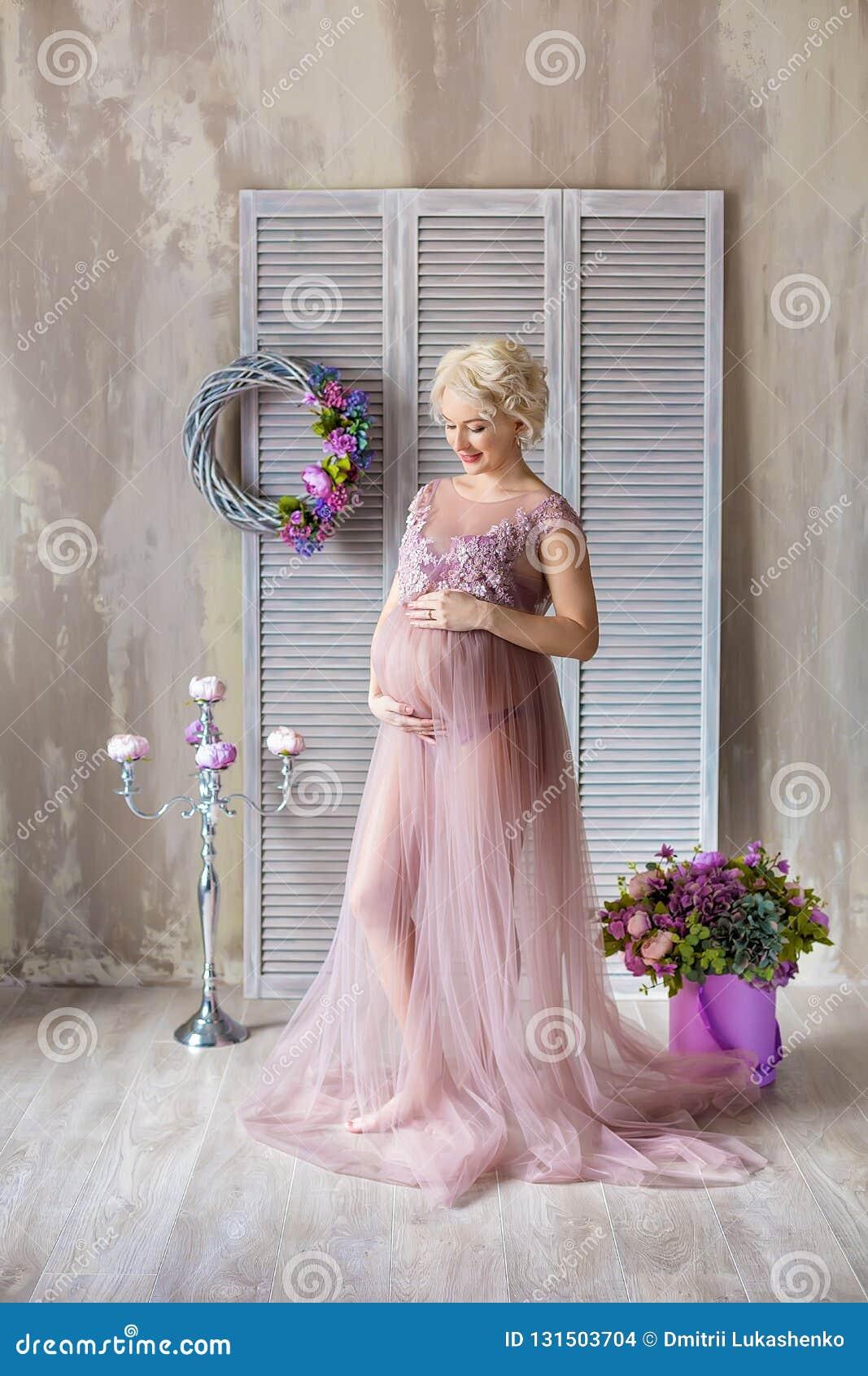 Gravidanza, maternità e concetto futuro felice della madre - donna incinta in vestito viola aerato con i fiori del mazzo contro v