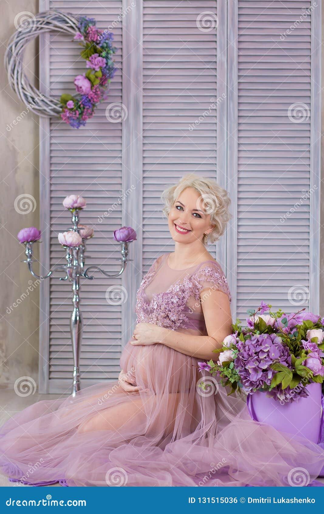 Gravidez, maternidade e conceito futuro feliz da mãe - mulher gravida no vestido violeta pairoso com as flores do ramalhete contr
