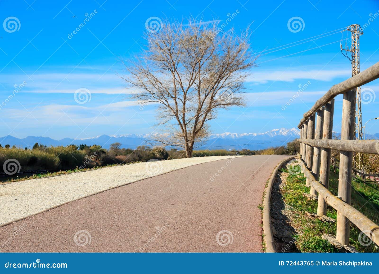 Gravier abandonné augmentant le chemin avec les crêtes de montagnes neigeuses à l arrière-plan