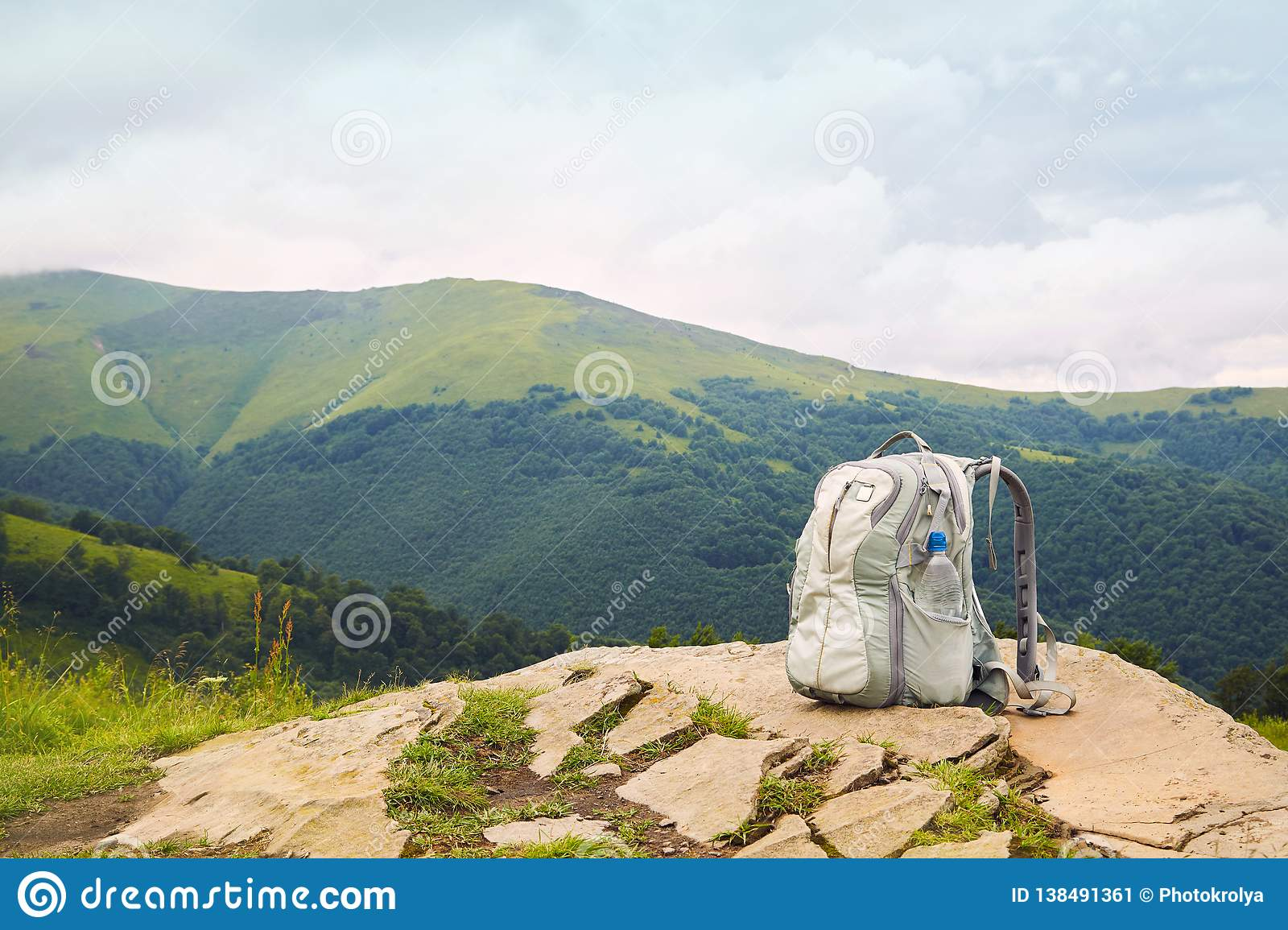 Gray backpack with a plastic bottle of drinking water on top of a mountain