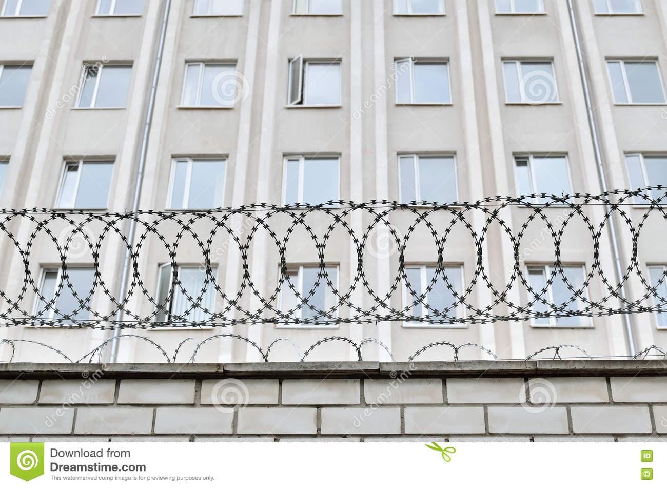 Gray Building Is Fenced With Barbed Wire. Symbol Of Dictatorial And ...