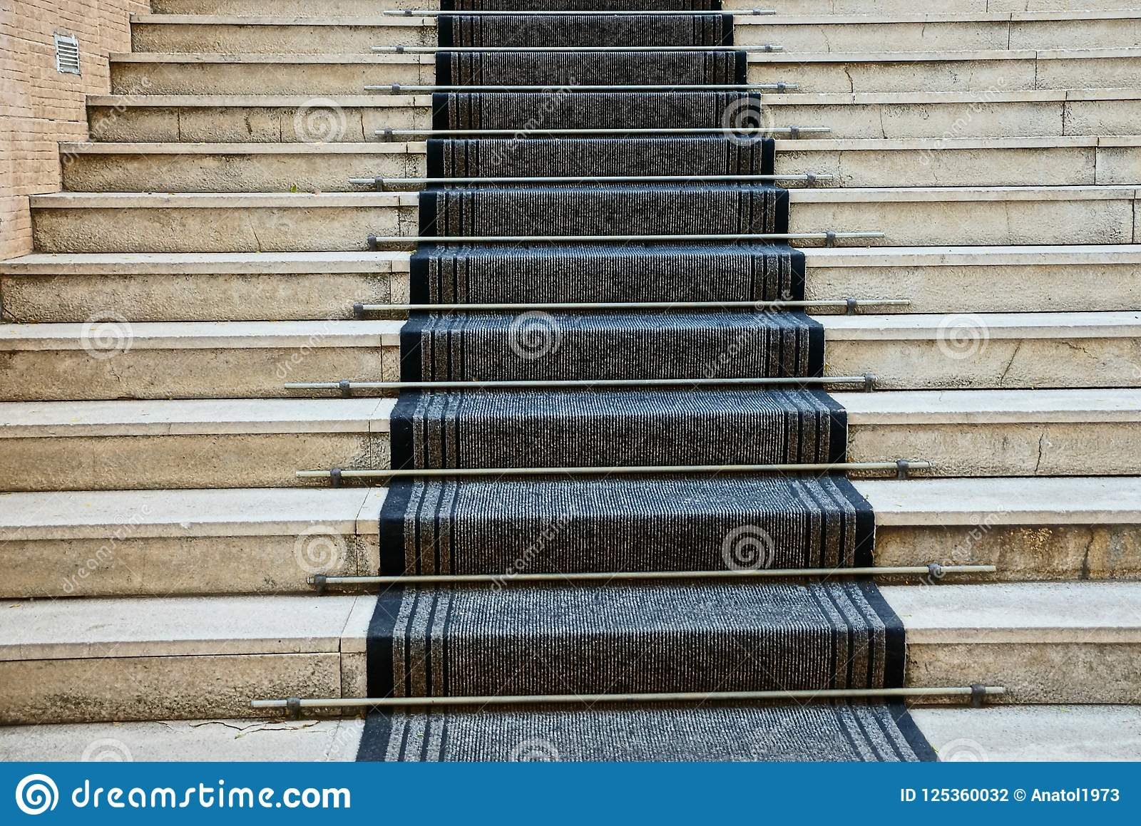Gray concrete steps of the stairs and black carpet track