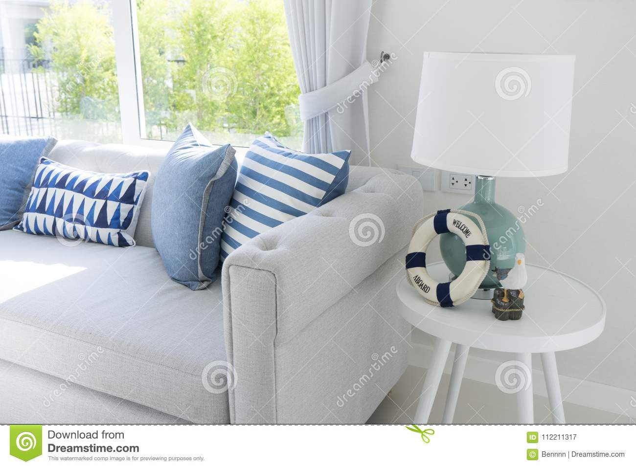 Gray couch with side table lamp in navy blue room