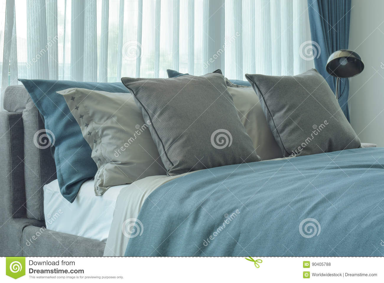 Gray and deep blue pillows setting on bed in deep blue color scheme