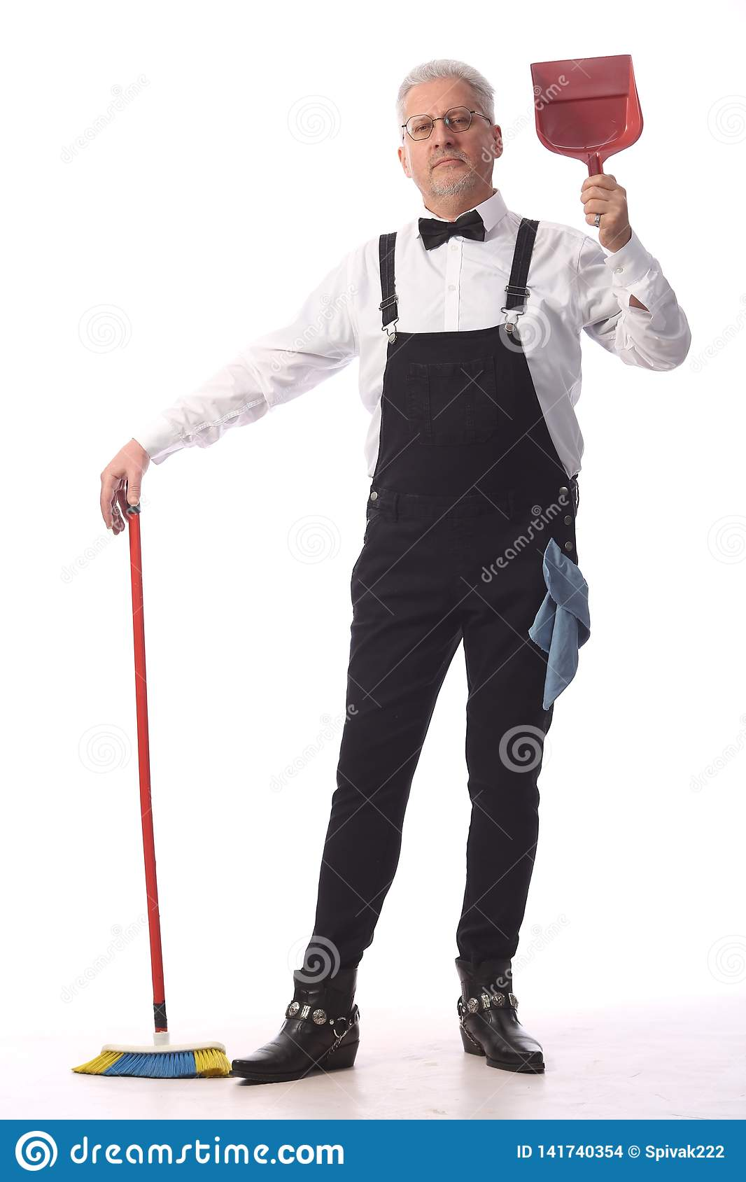 Gray-haired cleaner, janitor in a black jumpsuit with a mop and dustpan provides cleaning service, on white background
