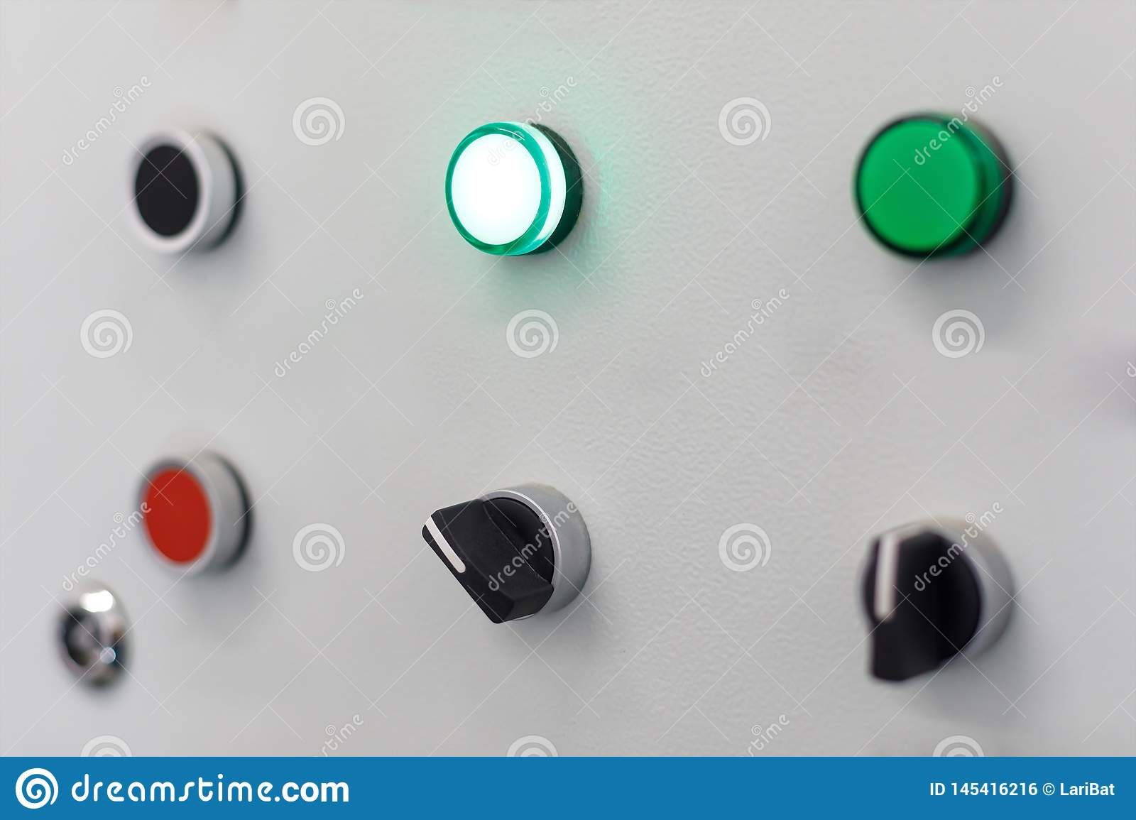 Gray panel with red and a few green buttons and black switches