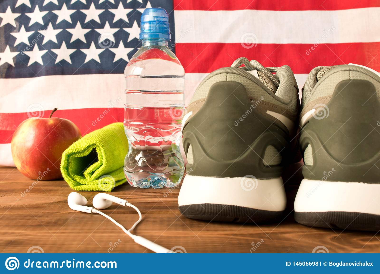 Gray sneakers and fitness accessories on the background of the American flag. The concept of the health of the nation. Selective