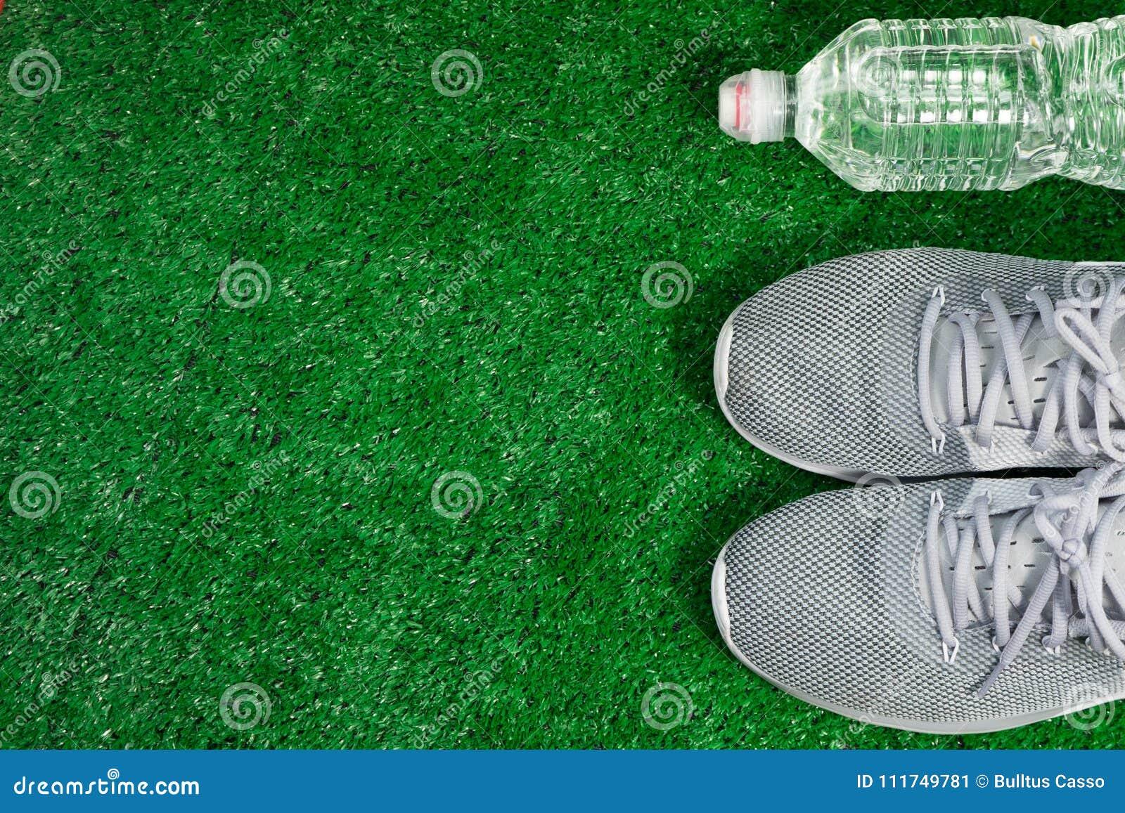 Gray Sports Running Shoes et bouteille de l eau sur l herbe verte
