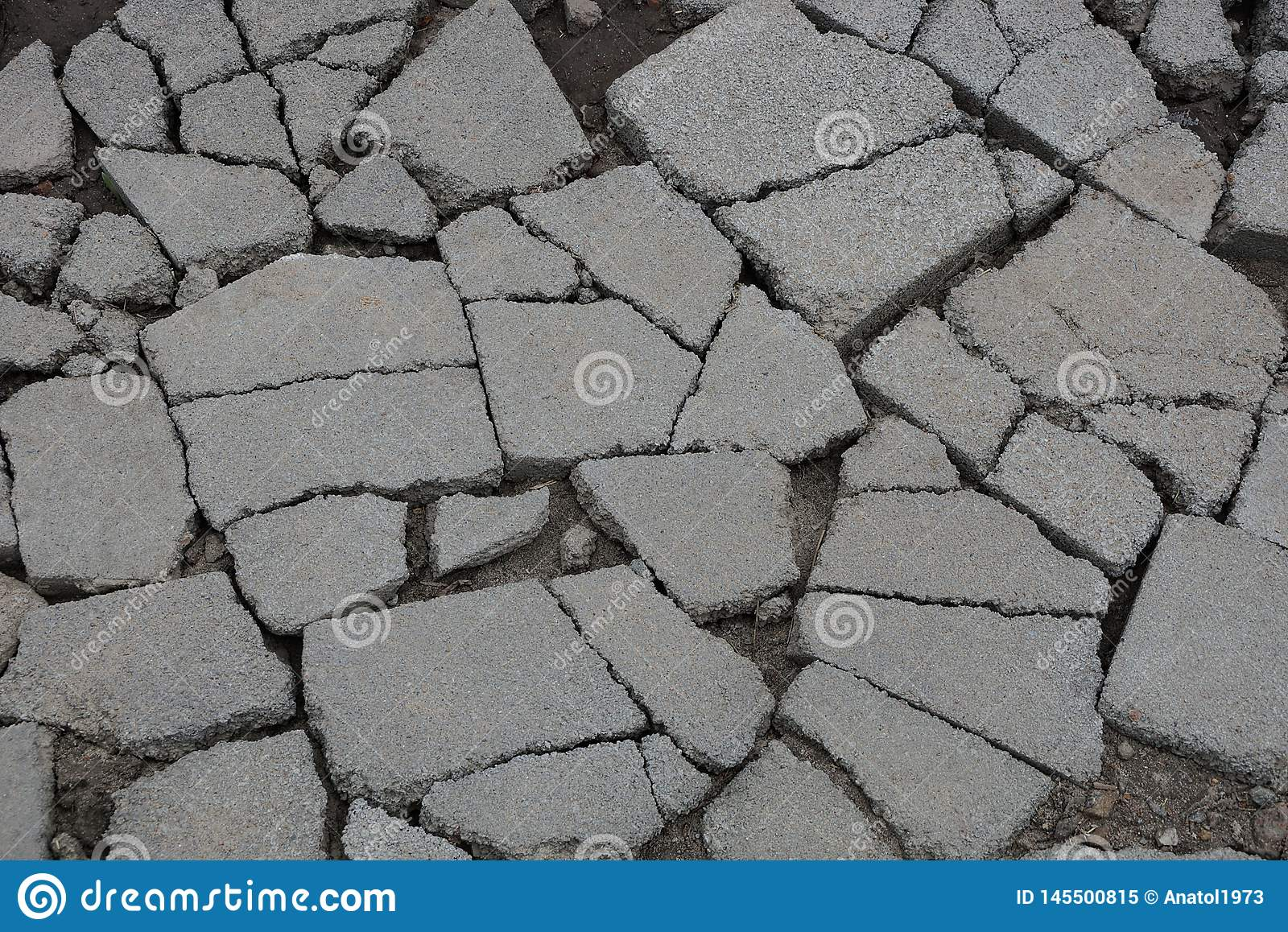 Gray stone texture of asphalt pieces with cracks on the road