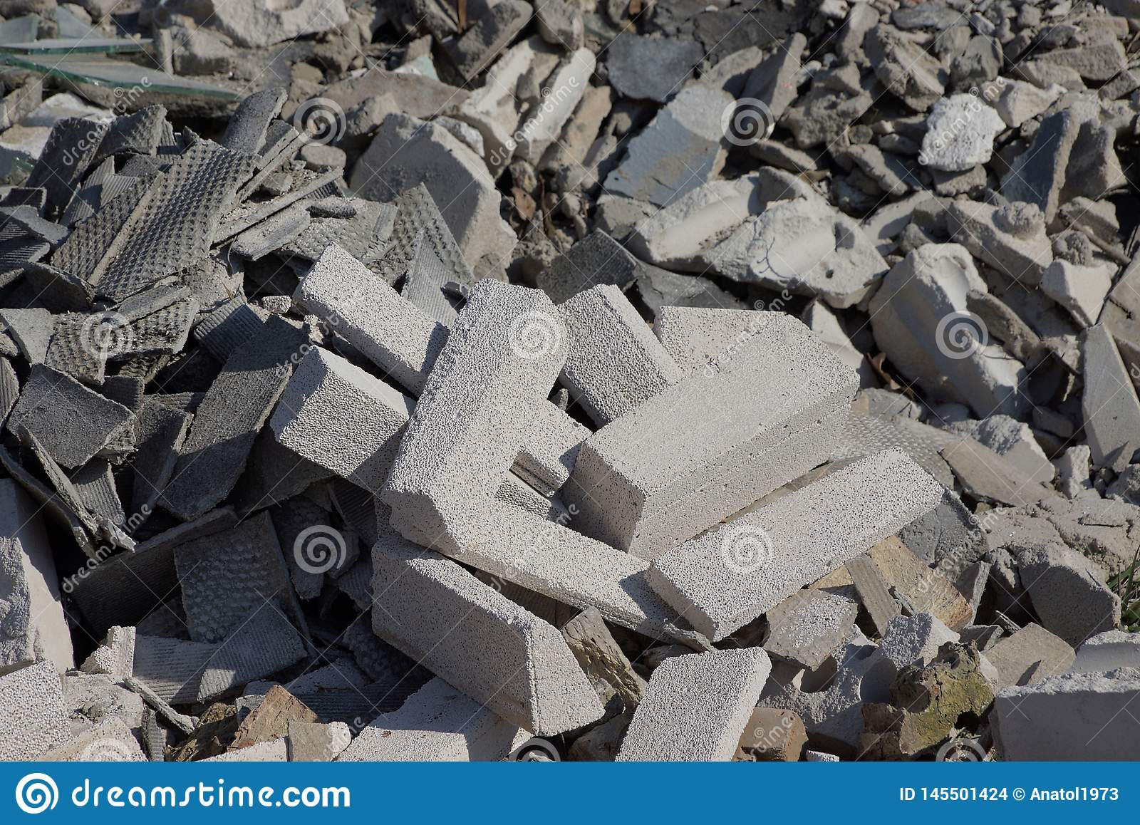 Gray stone background of pieces of bricks and concrete in a pile of garbage on the street