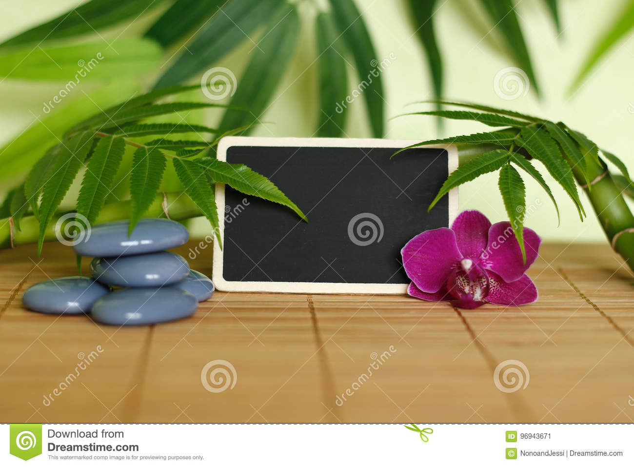 Gray stones arranged in Zen lifestyle with an orchid, a lighted candle, a bamboo branch and foliage and an empty message slate