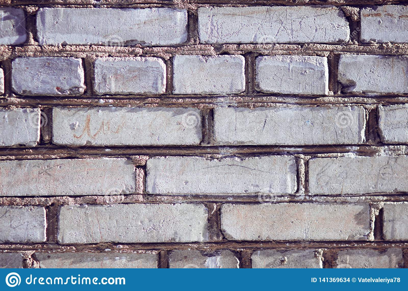 The gray wall of the building, built of rough uneven bricks