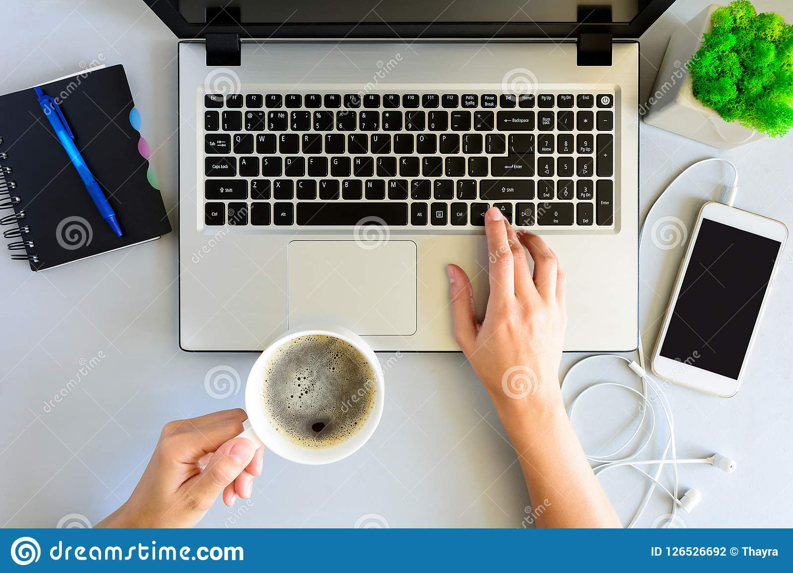 Gray wooden office desk table with laptop computer, smartphone,notebook, pen and cup of coffee. Female hands using a laptop