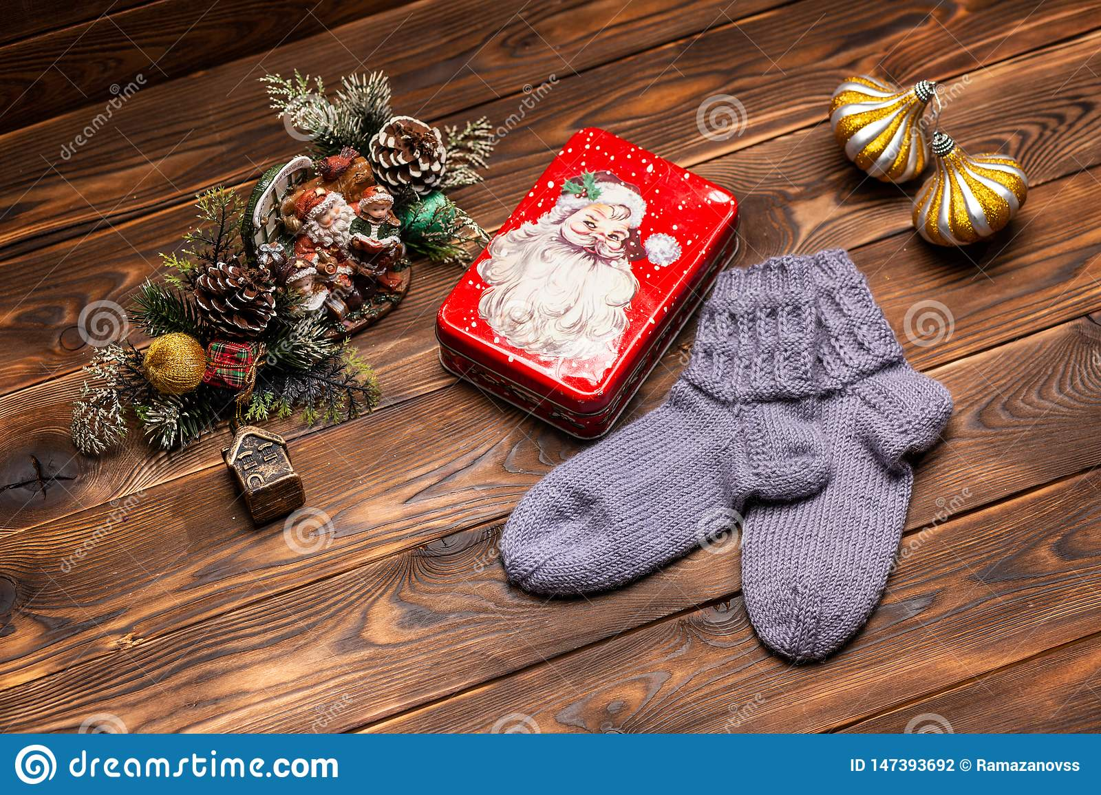 Gray woolen knitted socks, Christmas decorations and a metal box with the image of Santa Claus on a wooden background