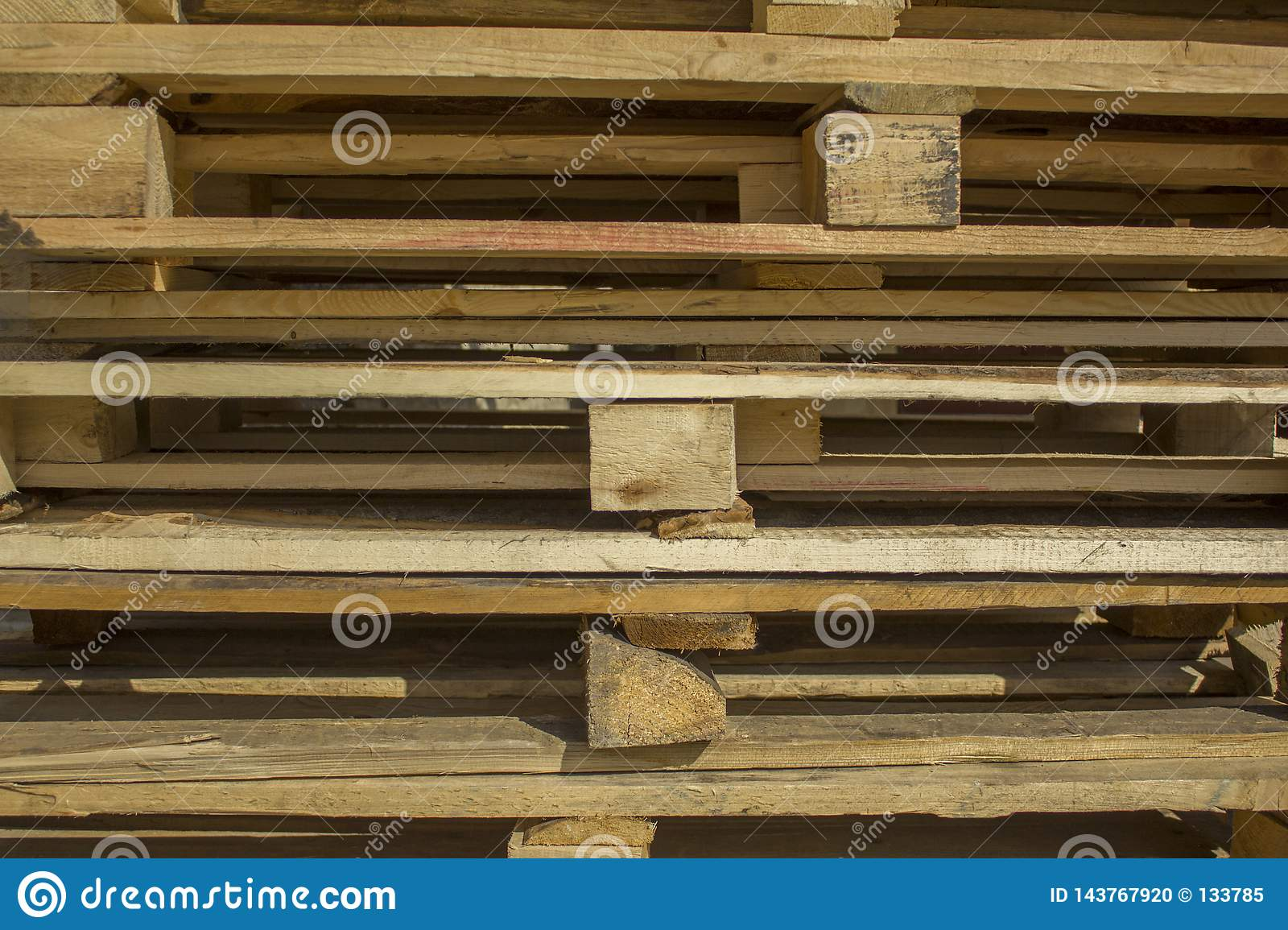 Gray and yellow wooden square bars and planks lie in rows, horizontal lines. rough surface texture