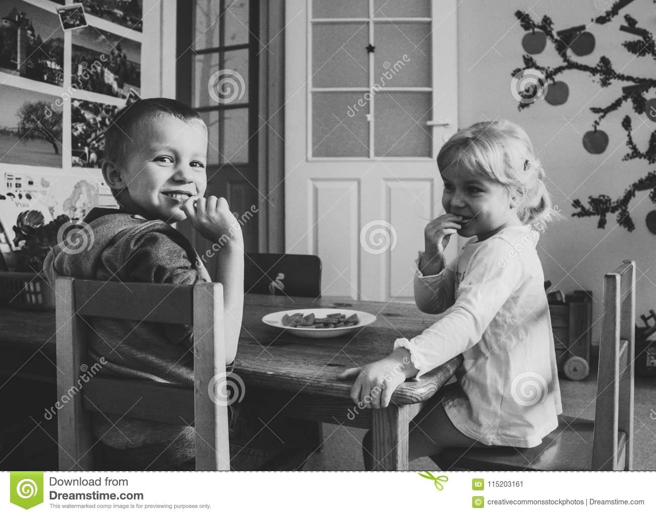 Grayscale Photo Of Two Kids Sitting On Dining Table Chairs Picture Image 115203161
