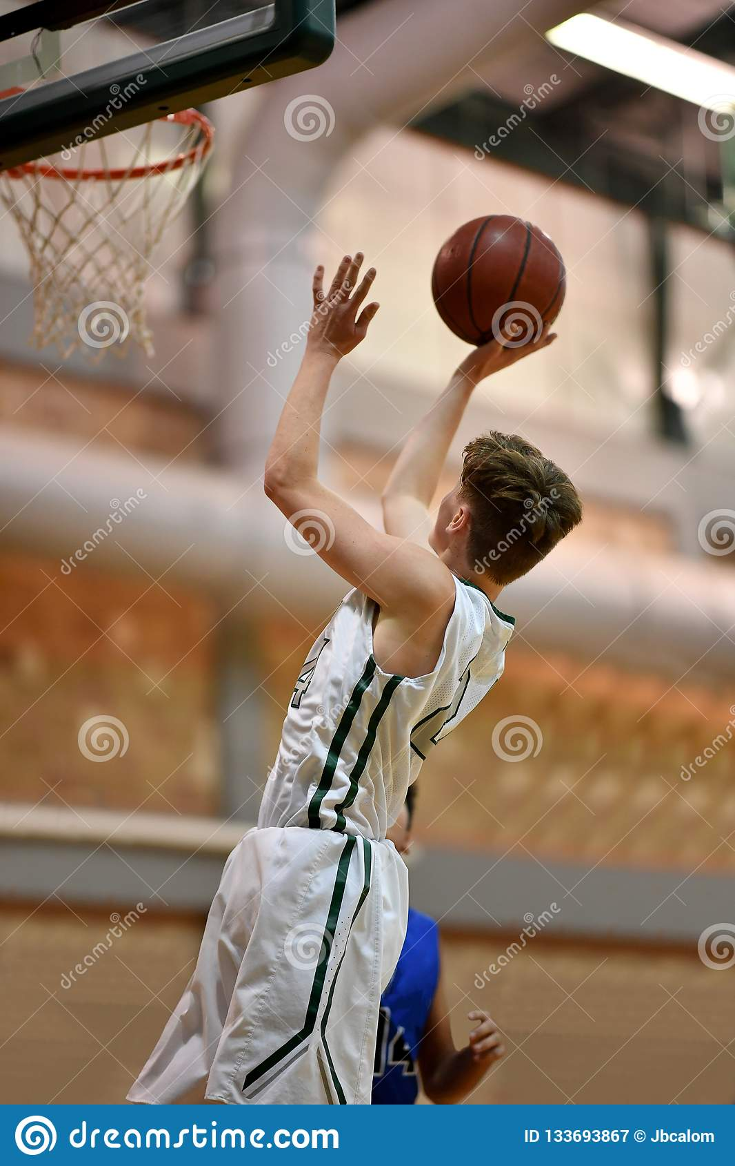 Great action shot of high school basketball player making an amazing play during a basketball game