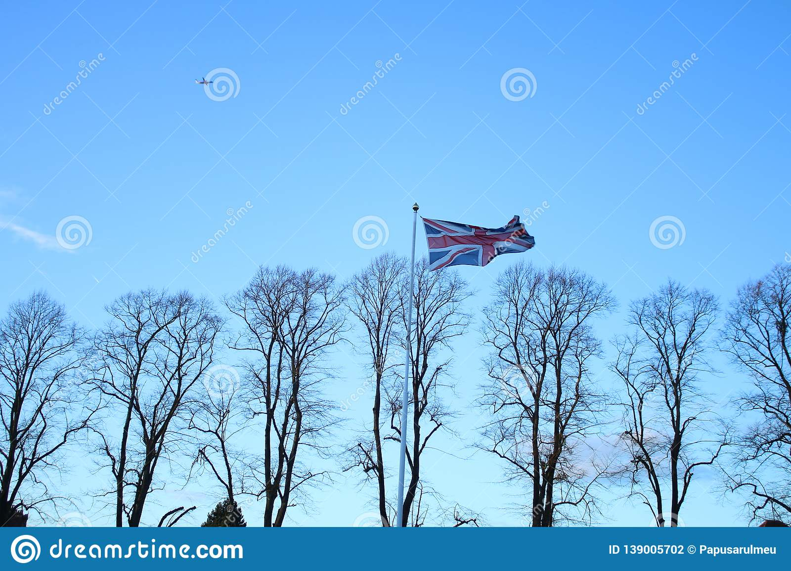 Great Britain`s flag fluttering in the wind. Wallpaper with clear blue sky