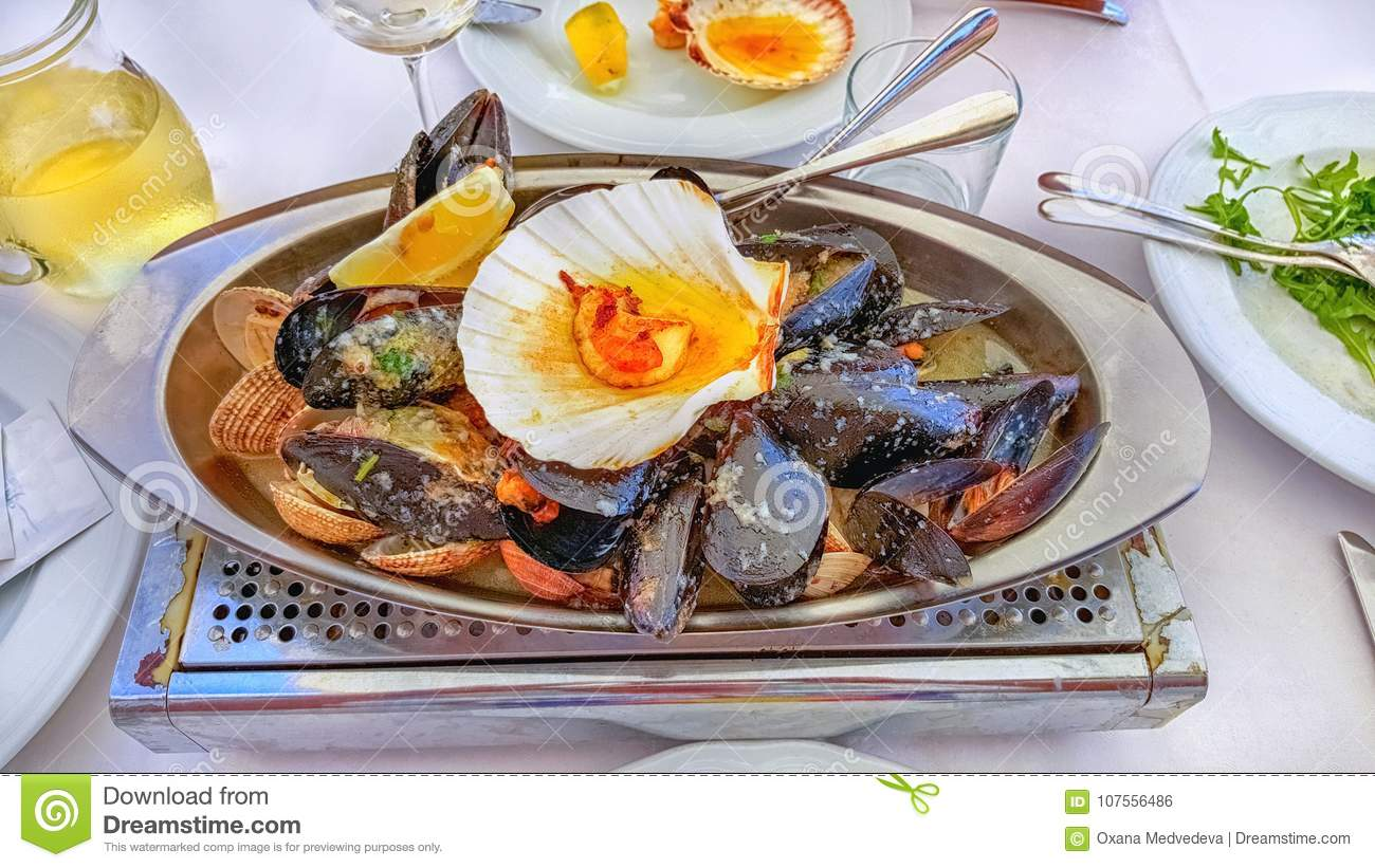 Great dish with the delicious oysters and scallops on ice with lime is served with champagne and herbs. Serving.