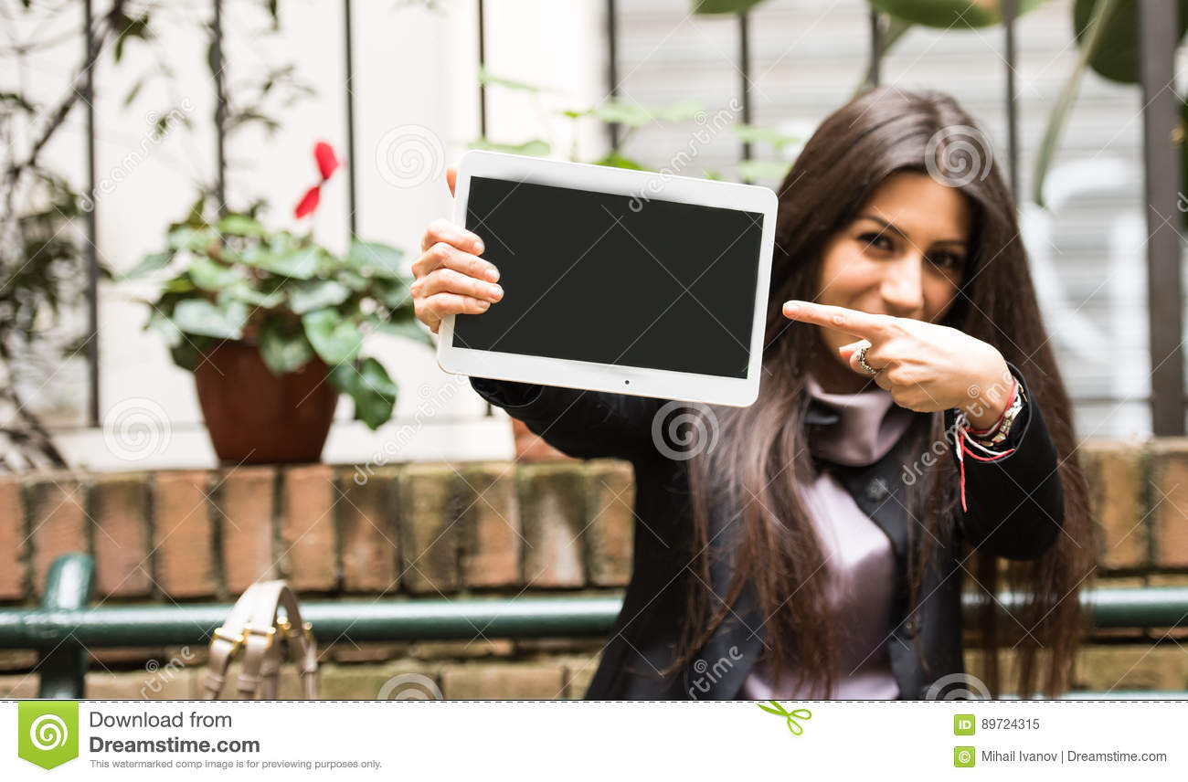 b1615bae3f3 Beautiful young brunette woman dressed in a business casual work suit  holding a white tablet with blank screen and making the peace sign. Amazing  new offers ...