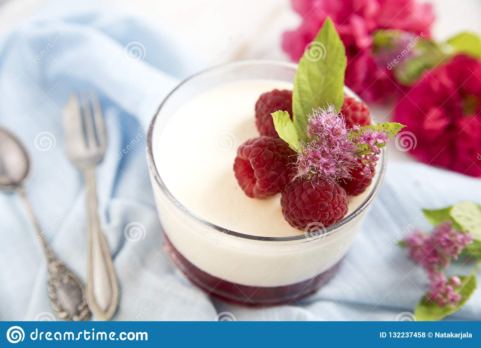Great panacotta dessert with raspberries, on a blue background and vintage spoon and fork.