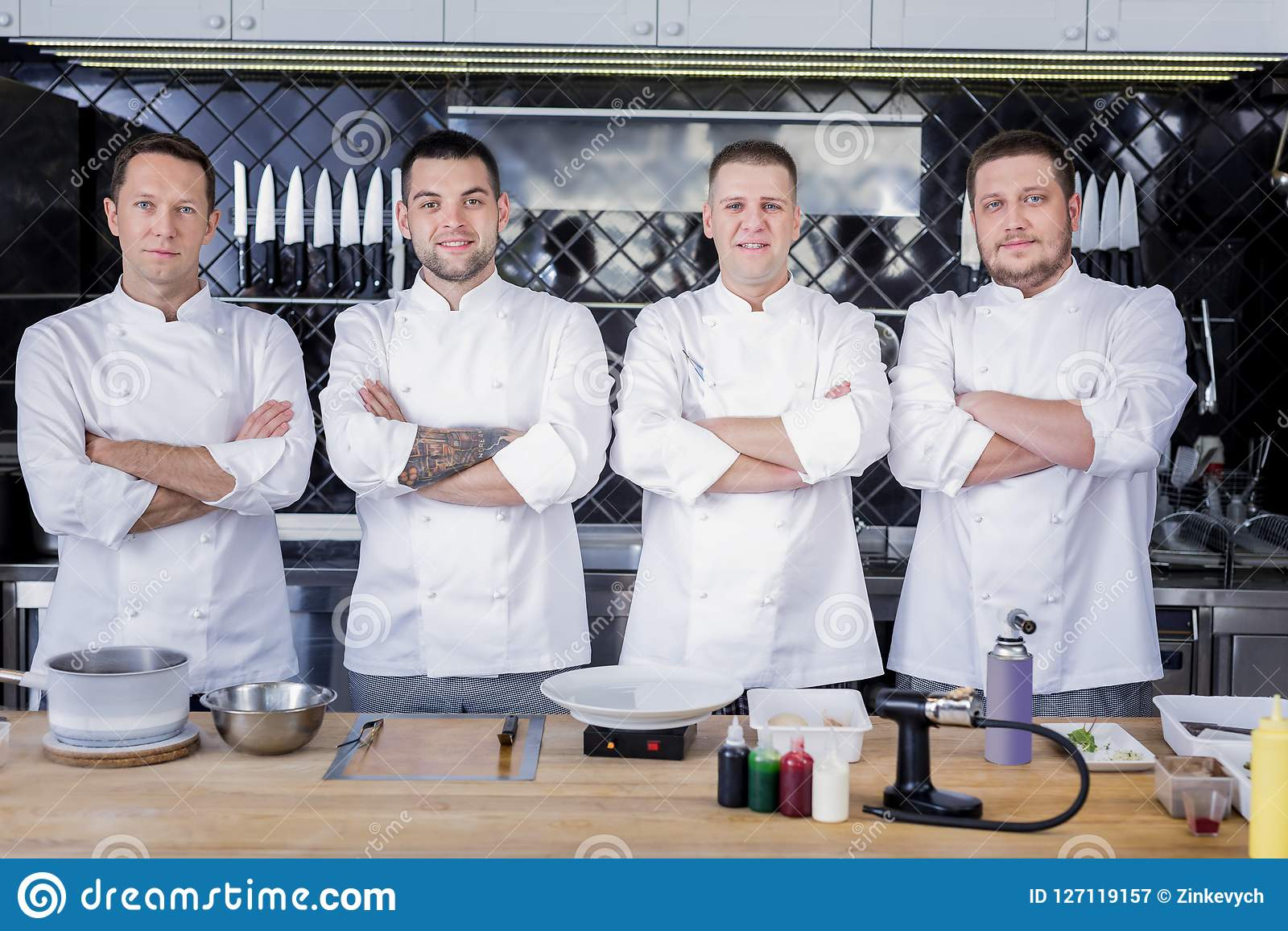 Great team of cooks standing in the middle of a kitchen