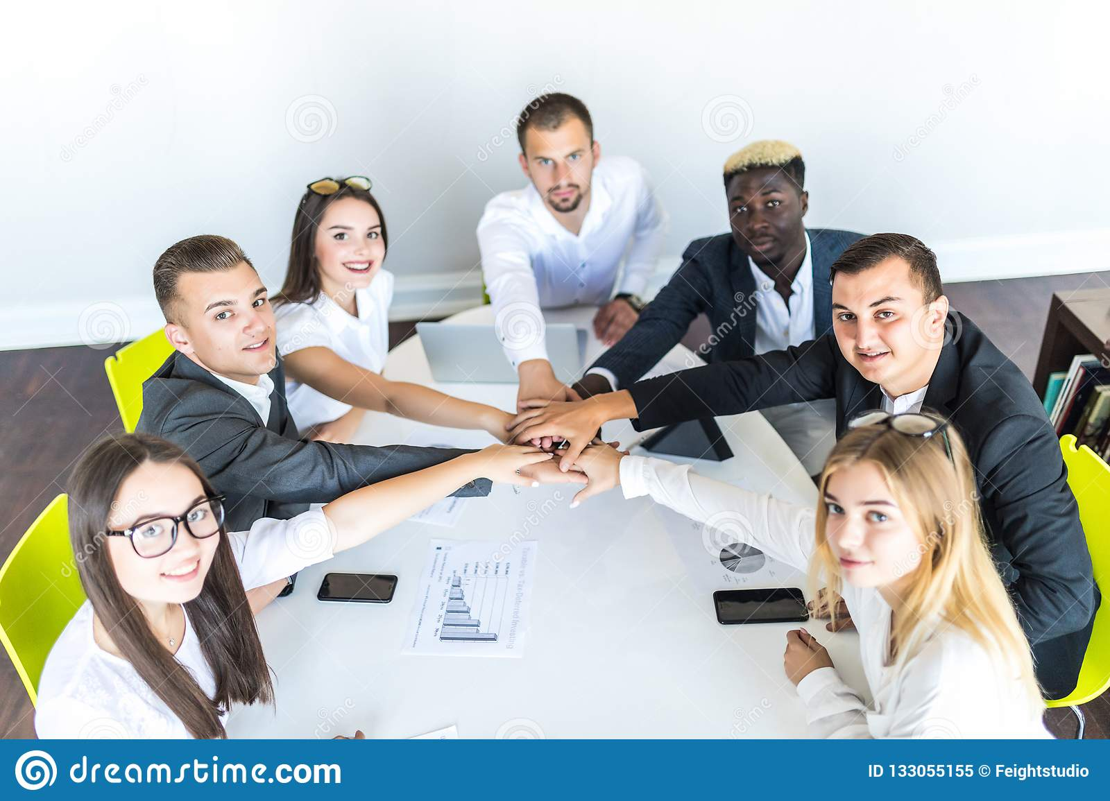 We are the great team. Group of happy business people holding hands together while sitting around the desk