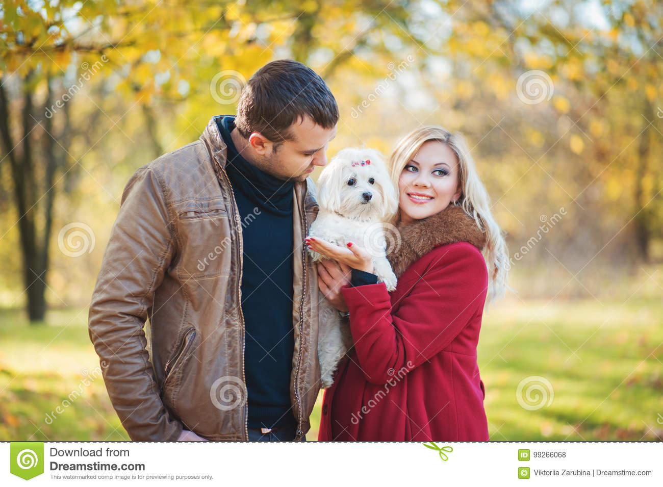 Great time for walk! Beautiful family couple with white cute Maltese dog spending time in autumn park