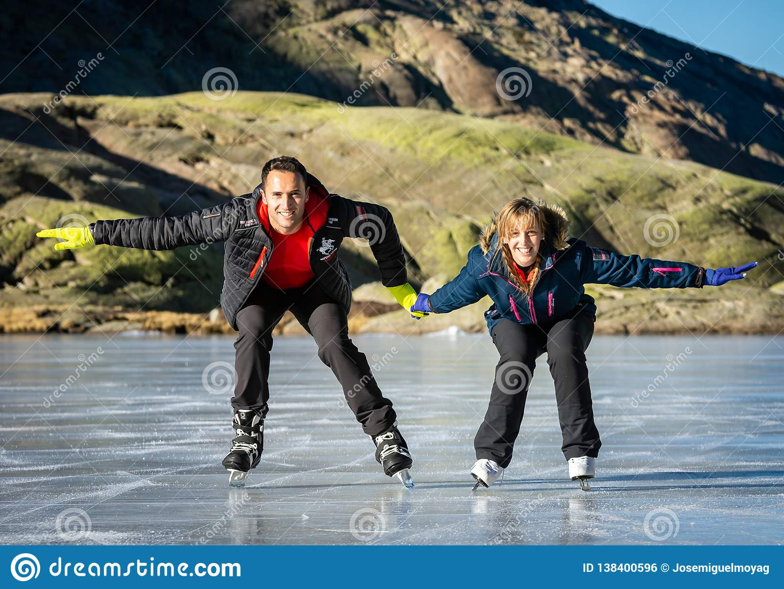 Gredos, Spain. 12-January-2019. Couple ice skating outdoors on a frozen lake during a lovely sunny winter day, Spain