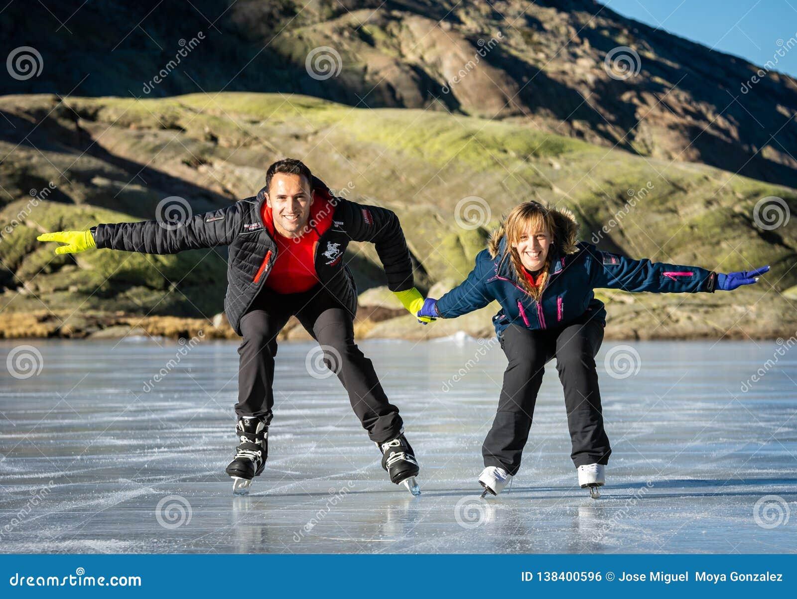 Gredos, Spanje 12-januari-2019 Paarijs die in openlucht op een bevroren meer tijdens een mooie zonnige de winterdag schaatsen, Sp