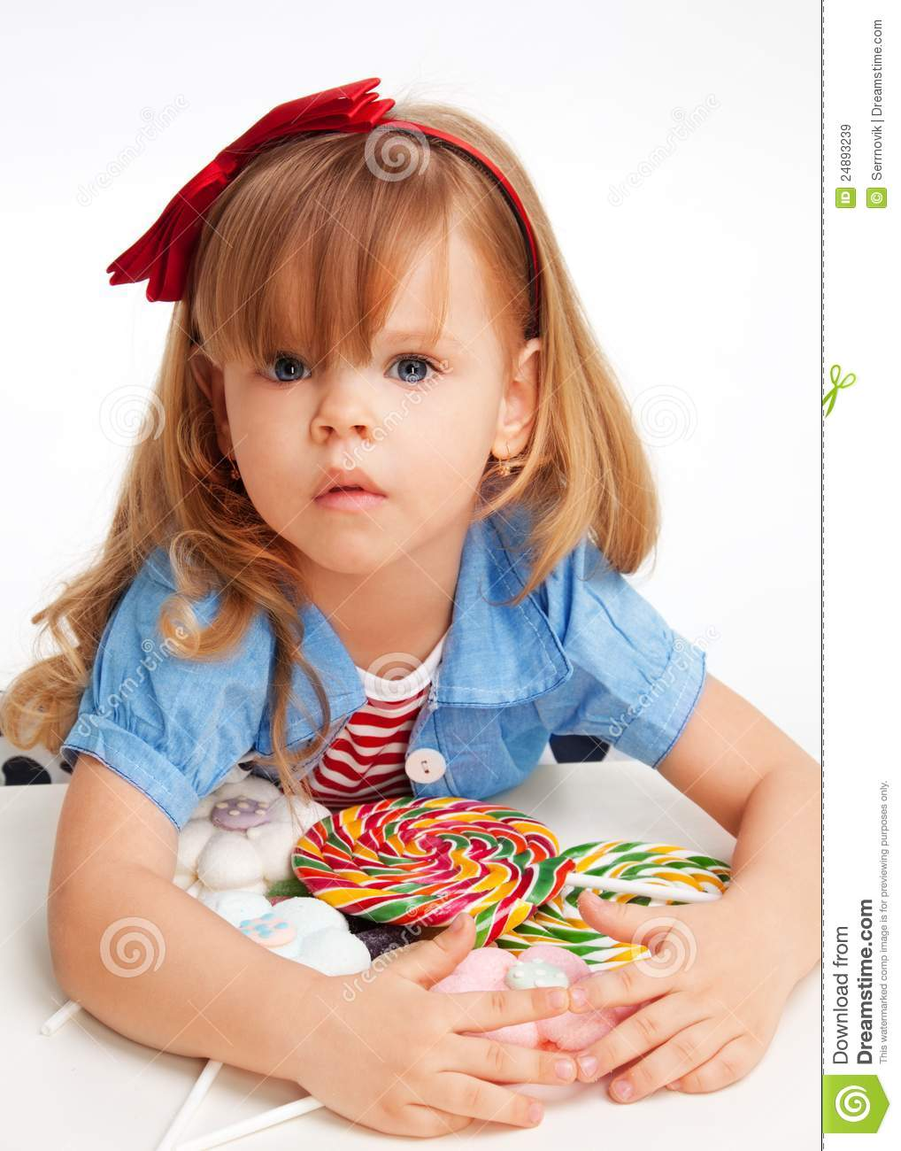 Greedy girl with pile of sweets laying on the table and with troubled ...